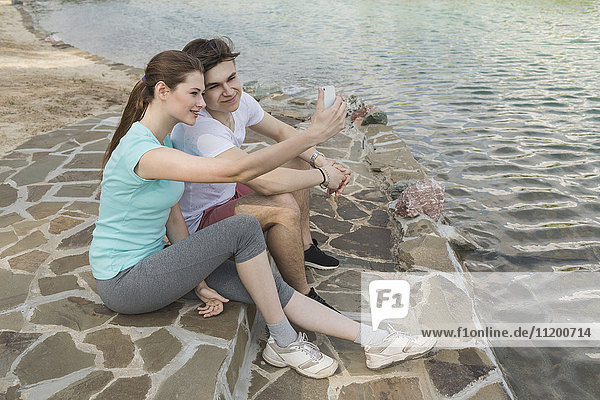 Liebende Paare,  die am See in der Stadt sitzen und Selfie nehmen.