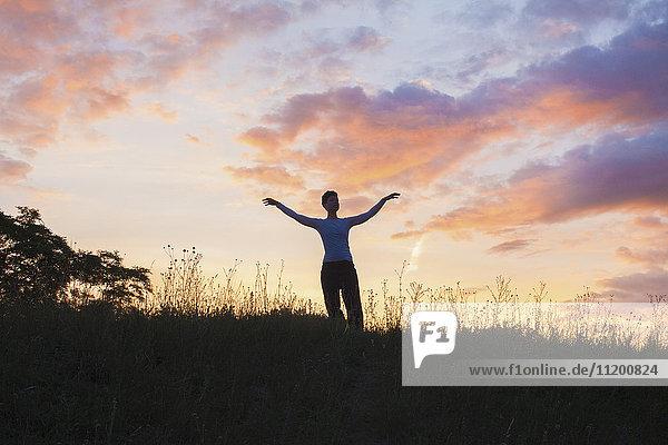 Frau steht mit ausgestreckten Armen auf grasbewachsenem Feld gegen den Himmel bei Sonnenuntergang.