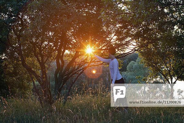 Frau praktiziert Entspannungsübungen auf dem Feld bei Sonnenschein