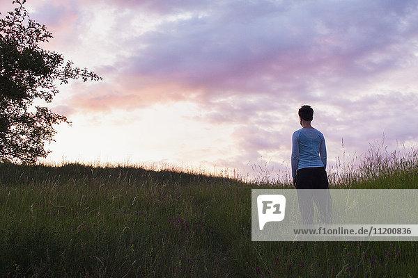Rückansicht der Frau  die bei Sonnenuntergang auf einem Grasfeld gegen den Himmel steht.