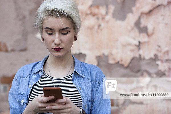 Schöne Frau beim Telefonieren an der alten Mauer