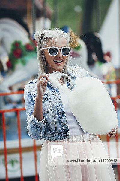 Modische junge Frau mit Sonnenbrille beim Essen von Zuckerwatte im Vergnügungspark