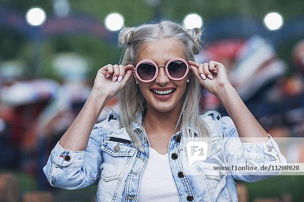 Portrait einer fröhlichen  modischen jungen Frau mit Sonnenbrille