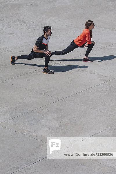 Hochwinkelansicht von Freunden  die an sonnigen Tagen die Beine auf dem öffentlichen Platz ausstrecken.