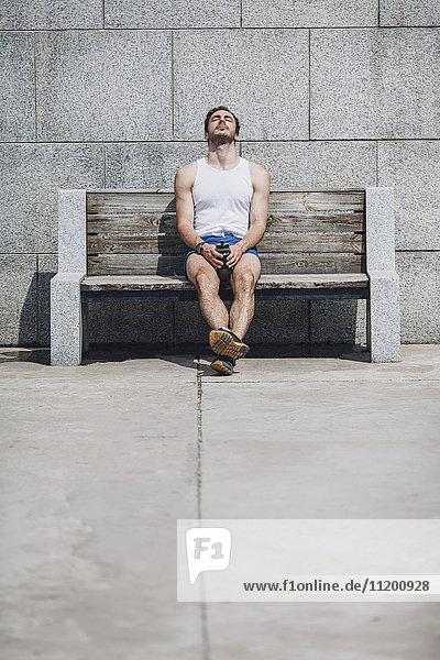 Müde junger Mann auf einer Holzbank an der Wand sitzend