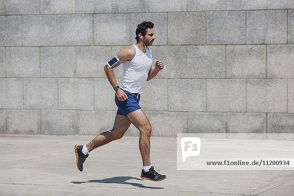 Entschlossener Sportler beim Joggen auf dem Bürgersteig an der Wand