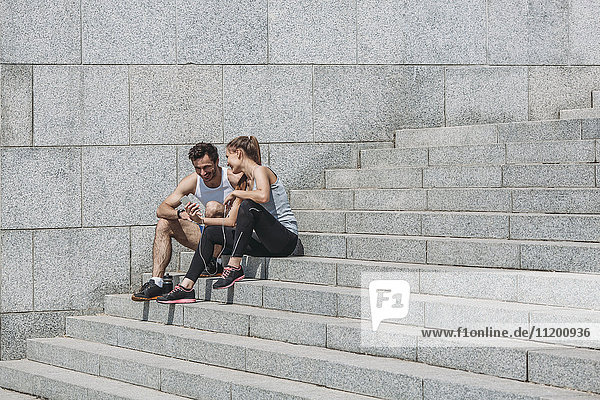 Fröhliche Frau  die ihrem Freund das Smartphone zeigt  während sie auf einer Treppe an der Wand sitzt.