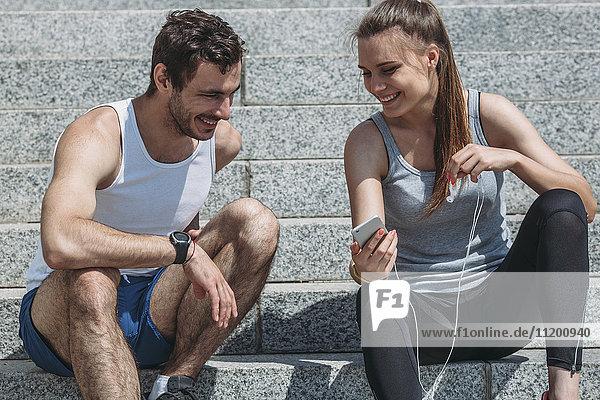 Fröhliche Frau zeigt Smartphone dem männlichen Freund beim Sitzen auf der Treppe