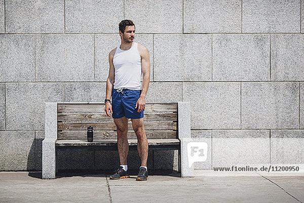 Seriöser Sportler steht an einer Holzbank auf dem Bürgersteig gegen die Wand.