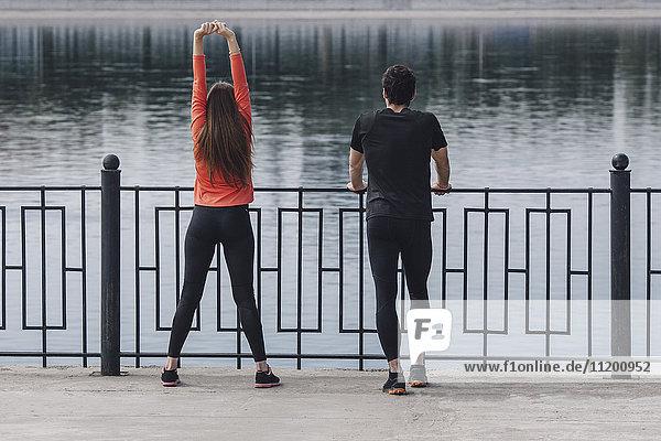 Rückansicht der Sportler auf der Promenade am See