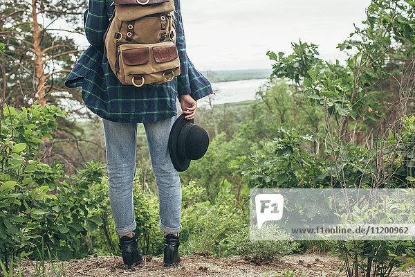 Niedriger Teil der Backpackerin  die den Hut hält  während sie im Wald steht.