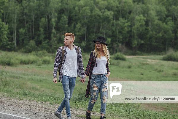 Paar  das sich an den Händen hält  während es am Straßenrand durch den Wald geht.