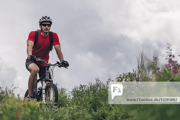 Entschlossener Mann auf dem Mountainbike gegen den bewölkten Himmel