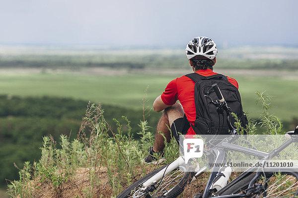 Rückansicht des Mannes  der mit dem Mountainbike auf dem Hügel sitzt.