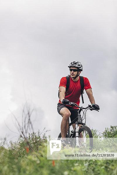 Selbstbewusster Mann auf dem Mountainbike gegen bewölkten Himmel