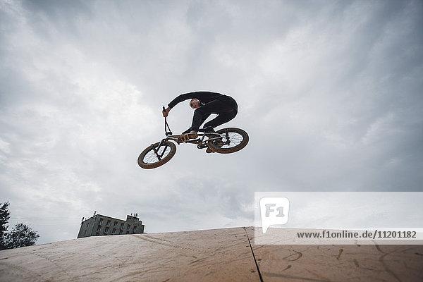 Low-Winkel-Ansicht des Teenagers beim BMX-Radfahren bei bewölktem Himmel
