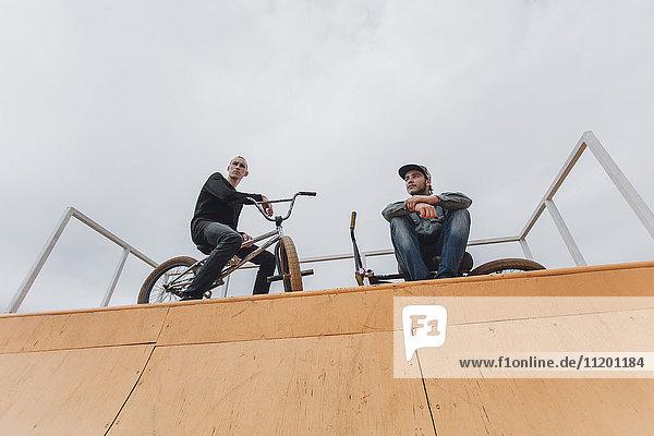 Flachwinkelansicht von Freunden mit Fahrrädern auf Rampe gegen den Himmel