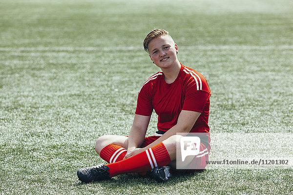 Porträt eines lächelnden Teenagers  der auf dem Feld sitzt.