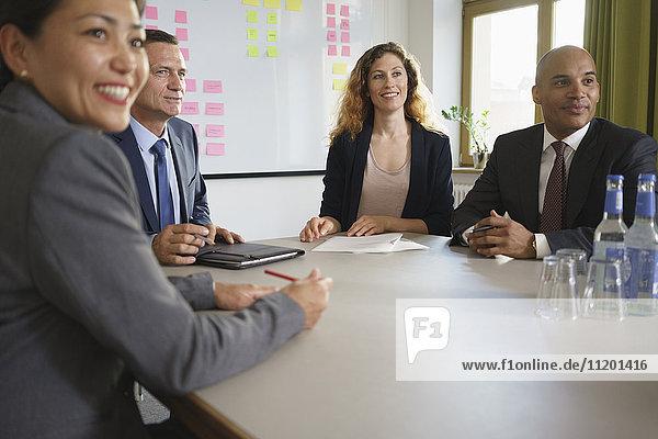 Lächelnde Geschäftsleute sitzen im Besprechungsraum