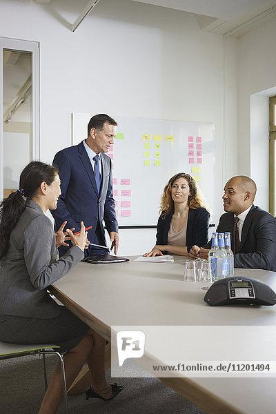 Fröhliche Geschäftsleute diskutieren im Meeting am Konferenztisch