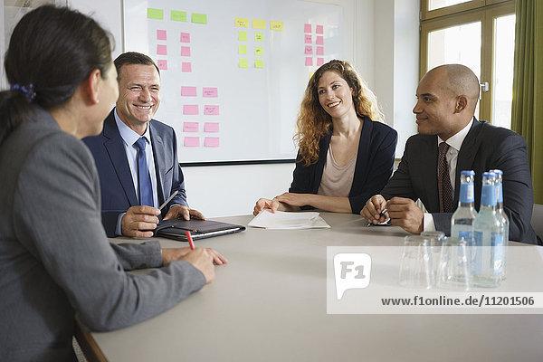 Lächelnde Geschäftsleute bei der Planung der Besprechung im Sitzungssaal