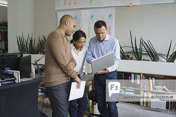 Geschäftsmann zeigt Laptop den Mitarbeitern während der Besprechung im Kreativbüro