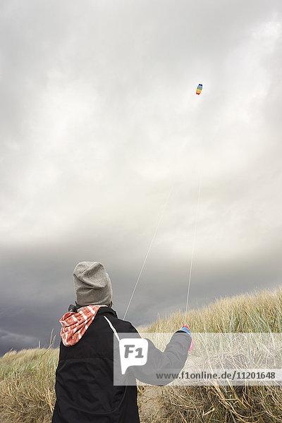 Rückansicht des Drachenfliegers gegen bewölkten Himmel