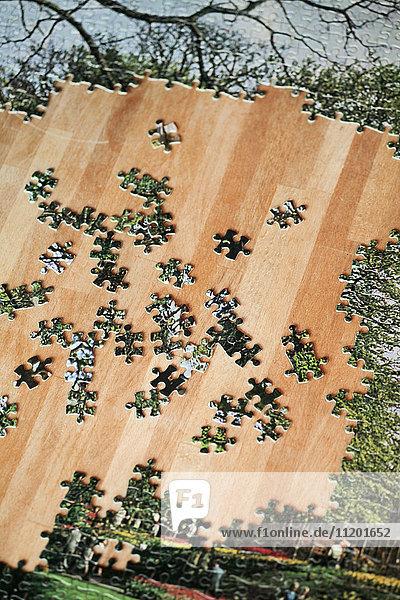 Hochwinkelansicht des Puzzles mit zerbrochenen Teilen auf Holztisch