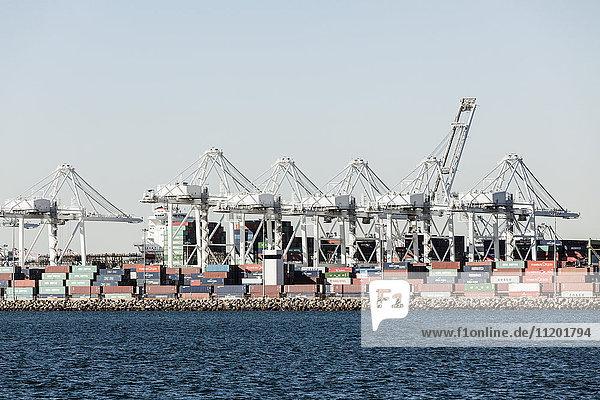 Frachtcontainer und Kräne auf dem Seeweg gegen den Himmel
