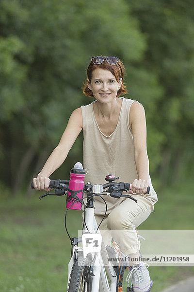 Portrait of smiling woman riding bicycle on field at park