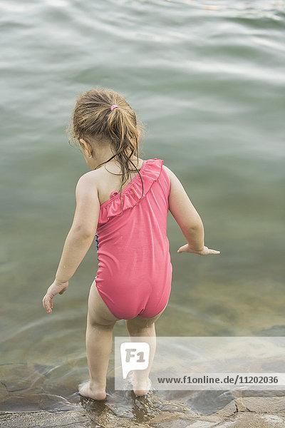 Rückansicht des am Seeufer stehenden Mädchens