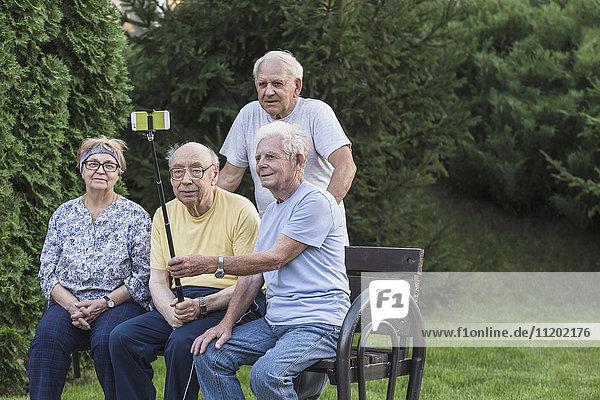 Lächelnde Seniorenfreunde  die sich mit einem Einbeinstativ auf der Parkbank selbstständig machen