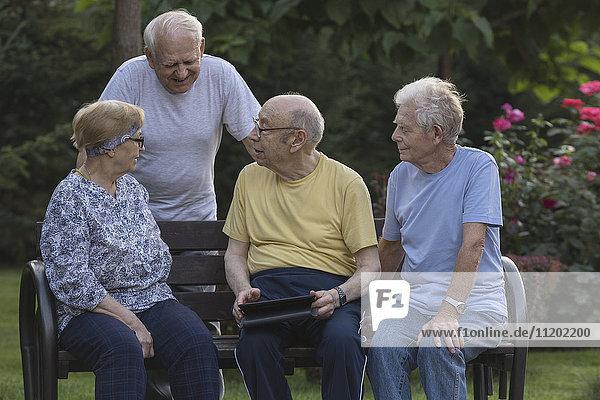 Lächelnde Senior-Freunde beim Gespräch mit dem digitalen Tablett auf der Parkbank