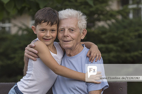 Portrait of smiling grandfather and grandson embracing while sitting at park bench