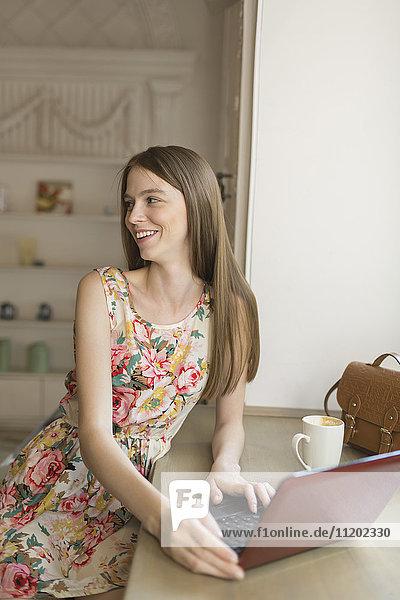 Glückliche Frau beim Sitzen am Fenster im Cafe mit Laptop