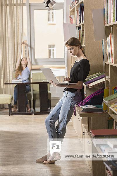 Volle Länge konzentriert mit dem Laptop  während man sich mit einem Freund im Hintergrund auf das Bücherregal stützt.