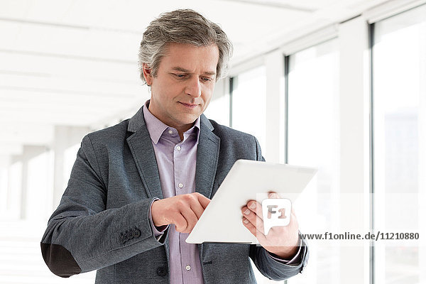 Mature businessman using digital tablet in new office