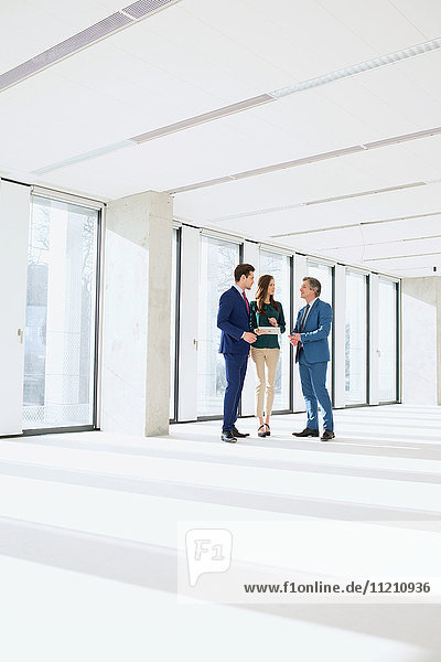 Full length of business people having discussion in empty office