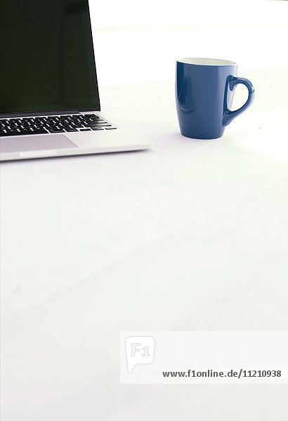 Laptop and coffee cup on white floor of office