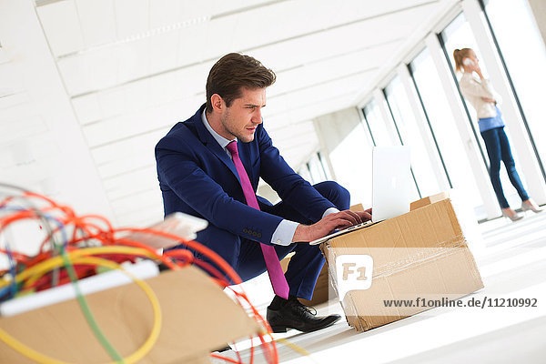 Young businessman crouching while using laptop on cardboard box in new office