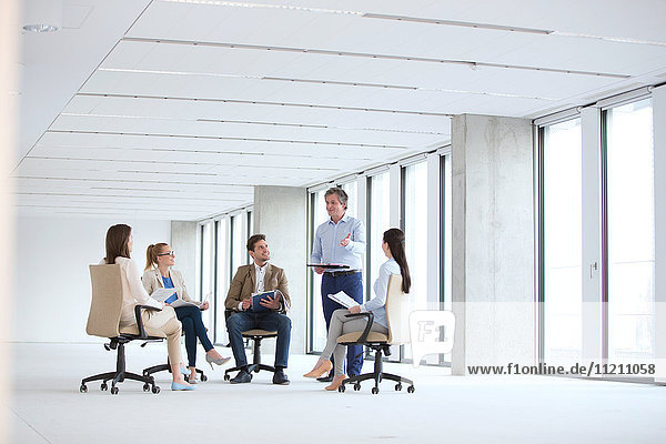 Mature businessman discussing with colleagues sitting on chair in new office