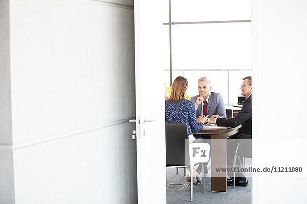 Businessmen and businesswoman in board room seen through open door at office