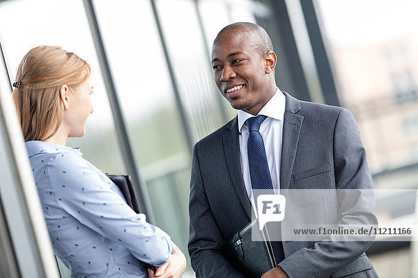 Smiling young businessman with female colleague on office balcony