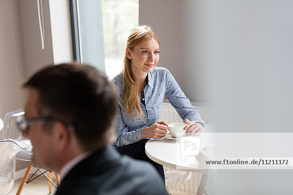 Young businesswoman having coffee in office cafeteria