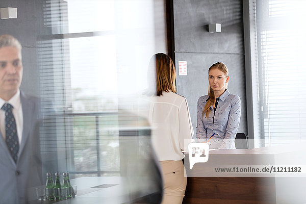 Young businesswoman with female receptionist in office