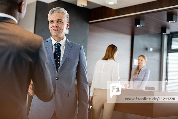 Mature businessman shaking hands with male colleagues in office