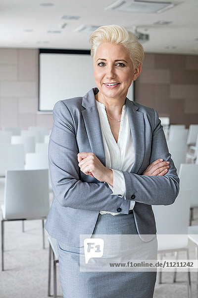 Portrait of confident businesswoman with arms crossed standing in seminar hall