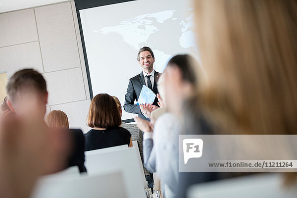 Confident public speaker looking at audience applauding during seminar