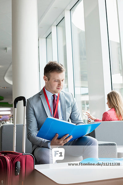 Businessman reading file while sitting at lobby in convention center