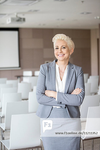 Portrait of businesswoman with arms crossed standing in seminar hall